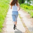 Girl runs in park view from the back. — Stockfoto
