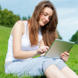 Stock Photo: Girl with tablet in park on grass.