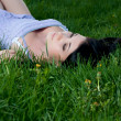 Woman lies on her back in grass. - Stock Photo