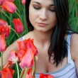 Woman looks at tulips. — Stock Photo