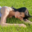 Woman lying on grass on bright sunny day. — Stock Photo