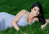 Beautiful brunette girl lying in grass. — Stock Photo