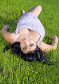 Beautiful girl lying on her back in lawn. — Stock Photo