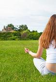 Girl meditates on lawn in garden. — Stock Photo