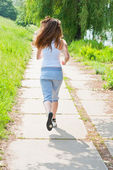 Girl runs in park view from the back. — Stock Photo