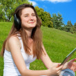 Girl with headphones and a tablet in the park. — Stock Photo