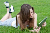 Girl with tablet on lawn. — 图库照片