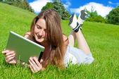 Jolie jeune femme avec tablette couché sur l'herbe. — Photo