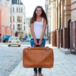 Girl with a big suitcase in the street. — Stock Photo