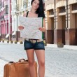 Girl with a suitcase looking at the map. — Stock Photo #11653862