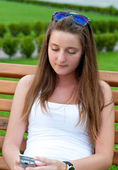Girl on the bench with mobile phone. — Stock Photo