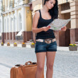 Girl with a suitcase looking at the map. — Stock Photo