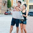 Young couple with a boy and a girl on the street map of the city — Stock Photo