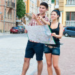 Foto Stock: Young couple with boy and girl on street map of city