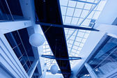 Modern business interior with glass ceiling in blue tones — Stock Photo