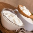 Cottage cheese in a plate and a spoon with cottage cheese — Stock Photo #12119327