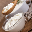 Cottage cheese in a plate and a spoon with cottage cheese — Stock Photo