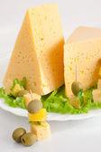 Kaas met groenen en olijven op een plaat — Stockfoto