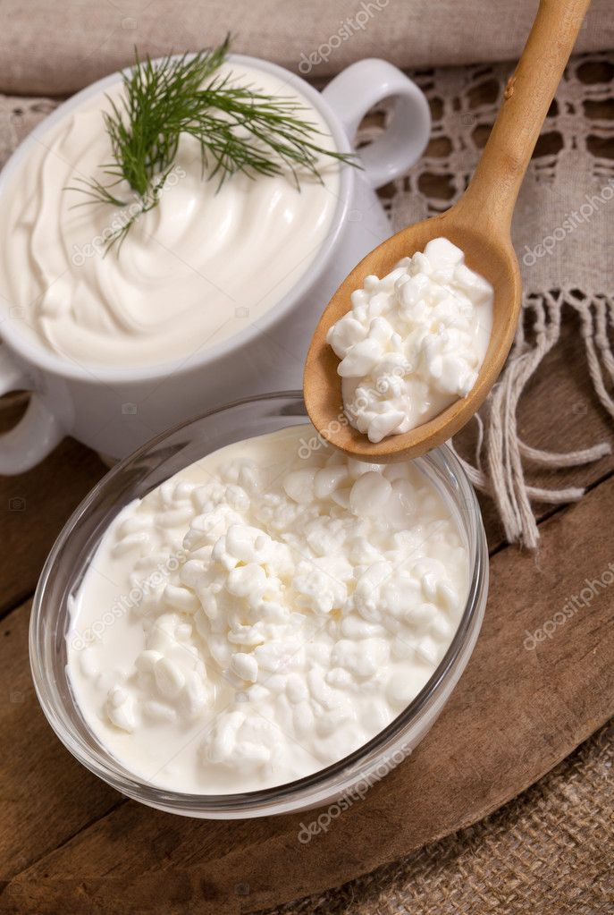 Cottage cheese in a plate and a spoon with cottage cheese — Stock Photo #12118495