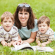 Mother and sons reading book outdoor — Stock Photo
