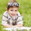 Beauty smiling child boy reading book outdoor - Stock Photo