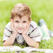 Beauty smiling child boy reading book outdoor — Stock Photo