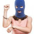 Woman in balaclava showing handcuffs on hands — Stock Photo