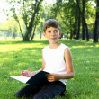 Stock Photo: Portrait of boy with book in park