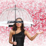 Pretty woman under umbrella with petals around her — Stock Photo