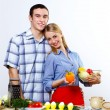 Husband and wife together coooking at home - Stok fotoğraf