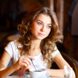 Photo: Young pretty woman sitting in restaurant