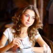 Stockfoto: Young pretty woman sitting in restaurant