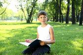 Retrato de un niño con un libro en el parque — Foto de Stock