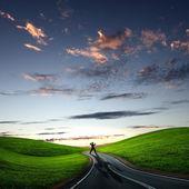 Man walking away at dawn along road — Stock Photo