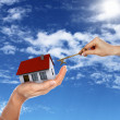 House and human hand against blue sky — Stock Photo #10831956