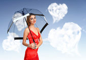 Pretty young woman with umbrella and hearts — Stock Photo