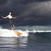 Jonge bedrijfspersoon surfen op de golven — Stockfoto