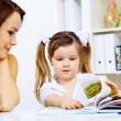 Little girl and her mother studying - Stockfoto