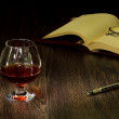 Cognac, cigar and an old book nearby — Stock Photo