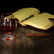 Cognac, cigar and an old book nearby - Stock Photo
