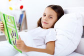 Girl with a book in bed at home — Stock Photo