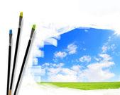 Paint brushes and landscape image — Stock Photo