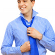 Young business man binding his blue tie — Stock Photo