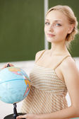 Teacher at school with a globe — Foto Stock