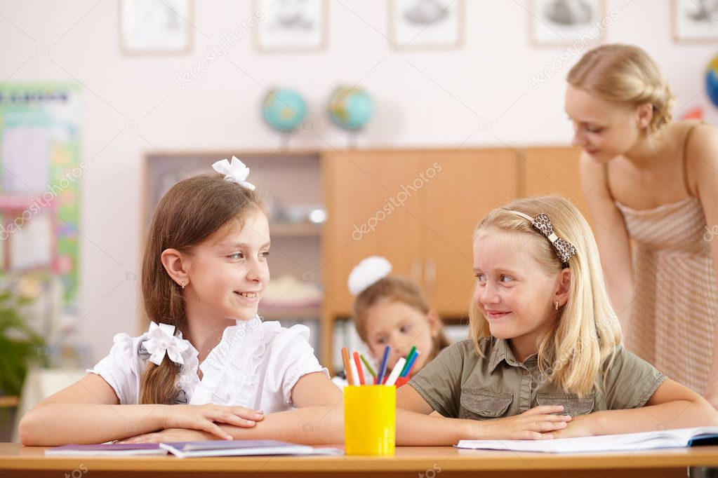 Young female teacher working with children at school — Stock Photo #12260566
