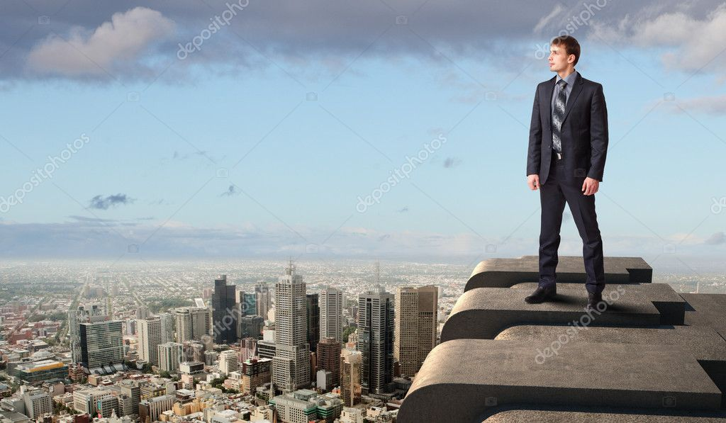 Business man standing high over a cityscape  — Stock Photo #12359996