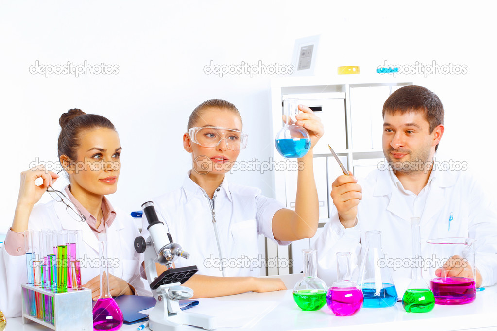 Team of scientists working with liquids in laboratory — Stock Photo #12360064
