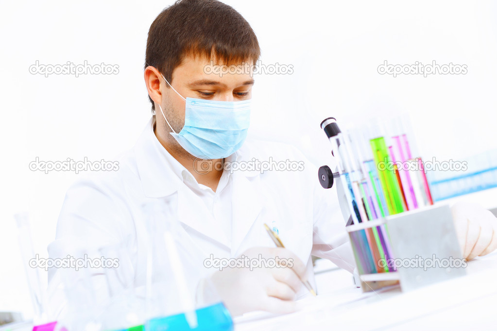 Young male scientist working with liquids in laboratory  Stock Photo #12360098