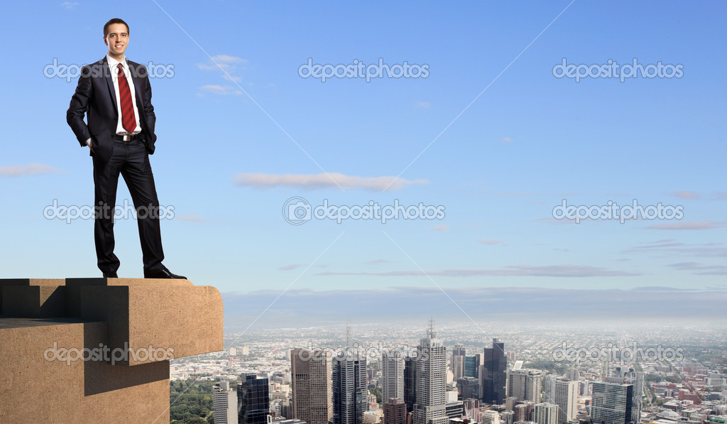 Business man standing high over a cityscape  — Stock Photo #12376785