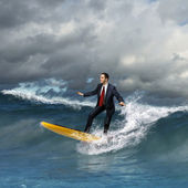 Young business person surfing on the waves — Stock Photo
